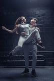 Jeunes danseurs agréables exécutant dans la salle noire Photographie stock libre de droits
