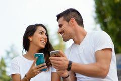 Jeunes datation de couples et d'utilisation smartphones ensemble Images stock