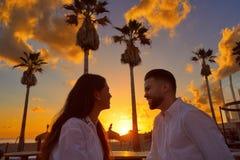 Jeunes de couples dans le lever de soleil de vacances de plage Photos libres de droits