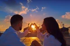 Jeunes de couples dans le lever de soleil de vacances de plage Images libres de droits