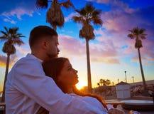 Jeunes de couples dans le lever de soleil de vacances de plage Photographie stock libre de droits