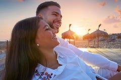 Jeunes de couples dans le lever de soleil de vacances de plage Photos stock
