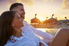 Jeunes de couples dans le lever de soleil de vacances de plage Image stock