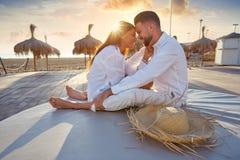 Jeunes de couples dans le lever de soleil de vacances de plage Images stock