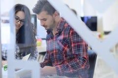 Jeunes de jeune entreprise, couples travaillant sur la tablette Image stock