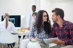Jeunes de jeune entreprise, couples travaillant sur la tablette Image libre de droits