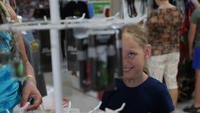 Jeunes de maman achats de fille ensemble et marchandises de choix dans le magasin clips vidéos