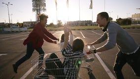 Jeunes de millennials emballant avec des caddies - amis fous heureux ayant l'amusement avec des chariots dans le parking Filles d banque de vidéos