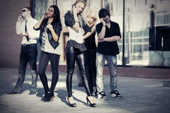 Jeunes de mode invitant des téléphones portables extérieurs Image libre de droits