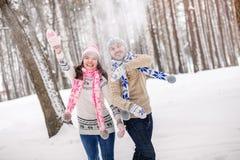 jeunes de sourire de l'hiver d'amour heureux de couples Jouer avec des boules de neige Images libres de droits