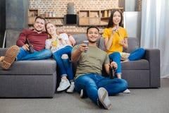 Jeunes de sourire s'asseyant ensemble et TV de observation Photos libres de droits