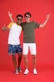 Jeunes deux amis d'hommes d'isolement au-dessus du fond rouge Image stock