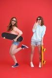 Jeunes deux amis de dames heureux tenant des planches à roulettes Photo libre de droits