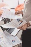 Jeunes documents d'entreprise et diagrammes de lecture de femme d'affaires dans le bureau photographie stock libre de droits
