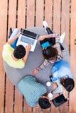 Jeunes employés employant la technologie du sans fil moderne tout en travaillant Photographie stock