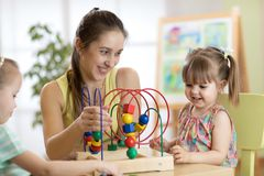 Jeunes enfants de aide d'institutrice gardienne avec des jouets photo stock