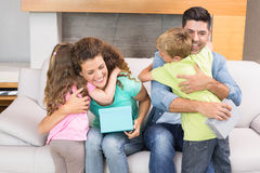 Jeunes enfants de mêmes parents donnant des présents à leurs parents Photographie stock
