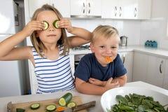 Jeunes enfants de mêmes parents doux jouant avec la cuisine de concombre et de carotte à la maison dans le mode de vie de frère e Image libre de droits