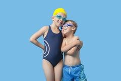 Jeunes enfants de mêmes parents heureux dans les vêtements de bain avec le bras autour au-dessus du fond bleu Photos stock
