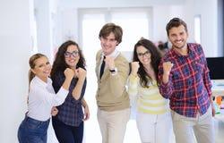 Jeunes entrepreneurs riants d'affaires dans l'habillement à la mode célébrant un succès Photo stock