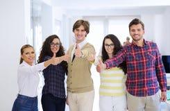 Jeunes entrepreneurs riants d'affaires dans l'habillement à la mode célébrant un succès Photo libre de droits