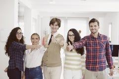 Jeunes entrepreneurs riants d'affaires dans l'habillement à la mode célébrant un succès Photographie stock libre de droits