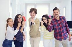 Jeunes entrepreneurs riants d'affaires dans l'habillement à la mode célébrant un succès Photographie stock