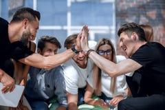 Jeunes entrepreneurs se donnant de hauts cinq lors d'une réunion informelle photographie stock libre de droits