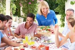Jeunes et aînés couples appréciant un repas Images libres de droits