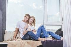 Jeunes et belles paires d'homme et de femme à la maison dans la chaleur et la COM Photographie stock