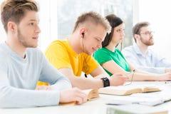 Jeunes et futés étudiants apprenant dans une salle de classe Image libre de droits
