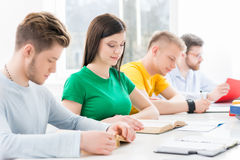 Jeunes et futés étudiants apprenant dans une salle de classe Photos libres de droits