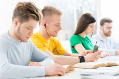 Jeunes et futés étudiants apprenant dans une salle de classe Photographie stock