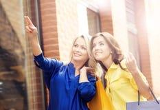 Jeunes et heureuses femmes avec des paniers dans la ville Image stock