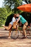 Jeunes et joyeux couples étreignant en parc avec la bicyclette et l'air Photo stock