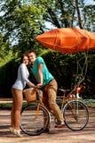 Jeunes et joyeux couples étreignant en parc avec la bicyclette et l'air Photographie stock libre de droits
