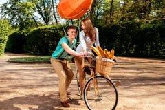Jeunes et joyeux couples apprenant à monter une bicyclette et un dirigeable o Images stock