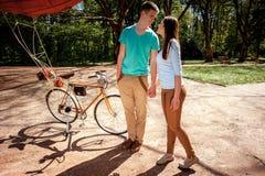 Jeunes et joyeux couples ayant l'amusement dans le parc avec la bicyclette et Photo libre de droits