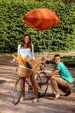 Jeunes et joyeux couples ayant l'amusement dans le parc avec la bicyclette et Image stock