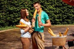 Jeunes et joyeux couples mangeant beaucoup de baguettes en parc Image stock
