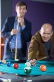 Jeunes et le vieil homme jouant avec enthousiasme des billards Photo stock