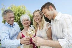 Jeunes et supérieurs couples grillant Champagne Flutes Outdoors Image libre de droits