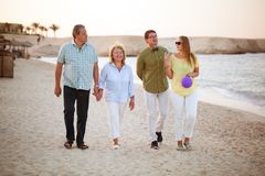 Jeunes et supérieurs couples marchant le long de la côte images stock