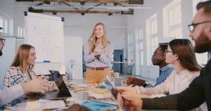 Jeunes expert du marketing heureux et entraîneur féminins blonds parlant, employés de motivation lors de cours moderne de formati banque de vidéos