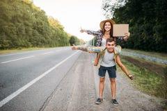 Jeunes faisant de l'auto-stop des ajouter au carton vide Image libre de droits