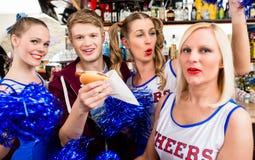 Jeunes fans de sports observant un jeu et buvant de la bière Photos libres de droits