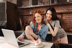 Jeunes femelles avec plaisir positives posant dans la cuisine Photos libres de droits