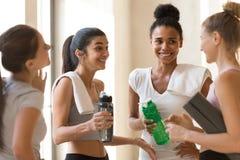 Jeunes femelles d'amis divers parlant après séance d'entraînement images stock