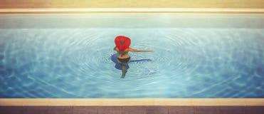 Jeunes femelles dans des chapeaux dans la piscine Images stock