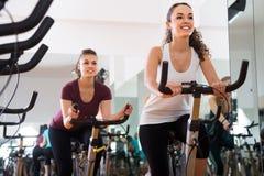 Jeunes femelles de la formation différente d'âge sur des vélos d'exercice Photographie stock